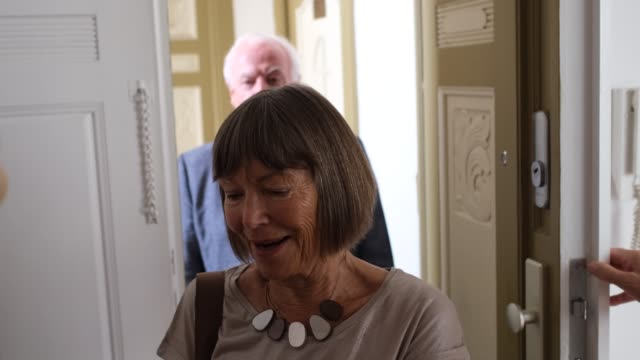 senior couple welcoming their guest at the doorway - arrivo video stock e b–roll