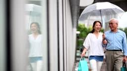 Senior couple window shopping during rainy season