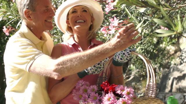 Senior couple with flower basket gardening.
