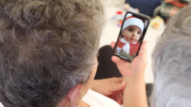 vídeos de stock e filmes b-roll de senior couple with mobile phone having video chat with family at christmas - natal