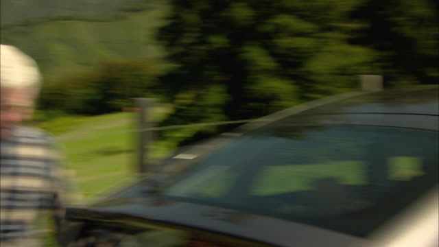 CU, PAN, Senior couple with picnic basket leaving car in mountain landscape, Big Sur, California, USA