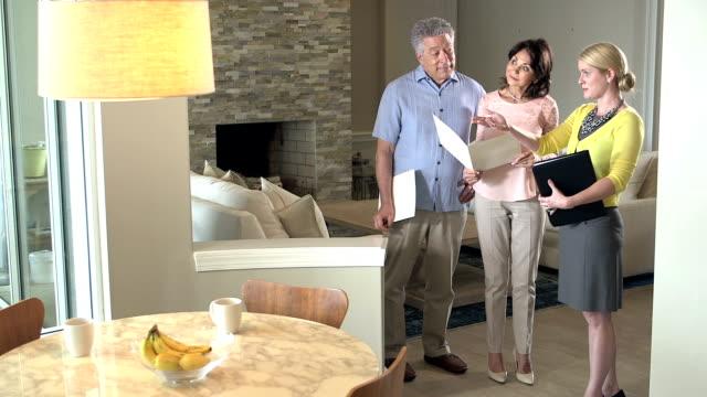 Älteres Paar mit Immobilienmakler in Haus