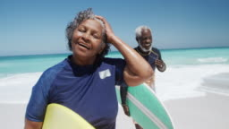 Senior couple with surfboards at the beach