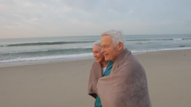 WS PAN Senior couple wrapped in blanket, walking on beach / Los Angeles, California, USA
