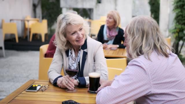 vidéos et rushes de couples aînés appréciant des boissons et la conversation au café - retraite