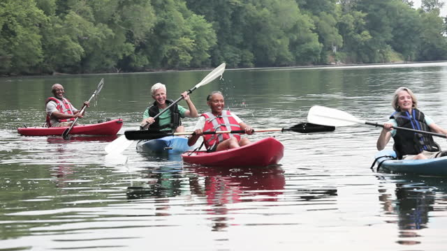Senior couples kayaking on river