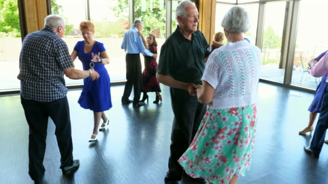 pan senior couples twirling during dance in community center - 70 79 years stock videos and b-roll footage