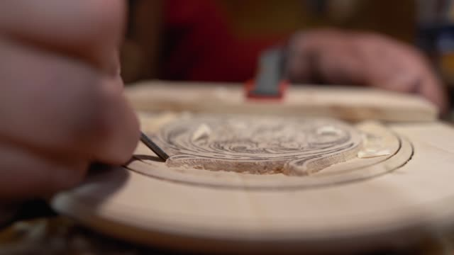 Senior craftsman engraving wooden plate