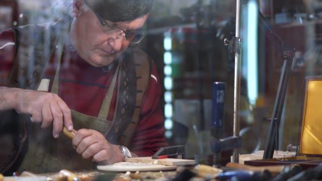 senior craftsman working at his craft shop - pensionati lavoratori video stock e b–roll