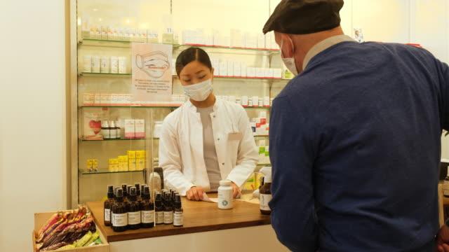 vidéos et rushes de client aîné achetant la médecine à la pharmacie - billet de banque