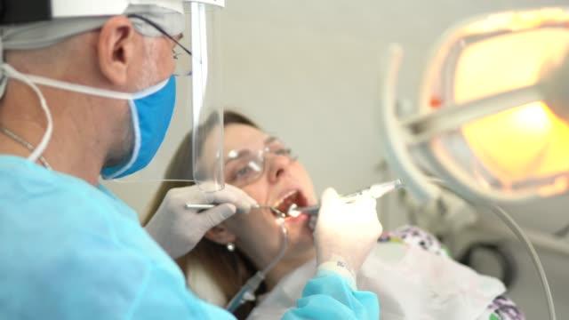 vídeos de stock, filmes e b-roll de dentista sênior examinando os dentes de uma jovem - dentista
