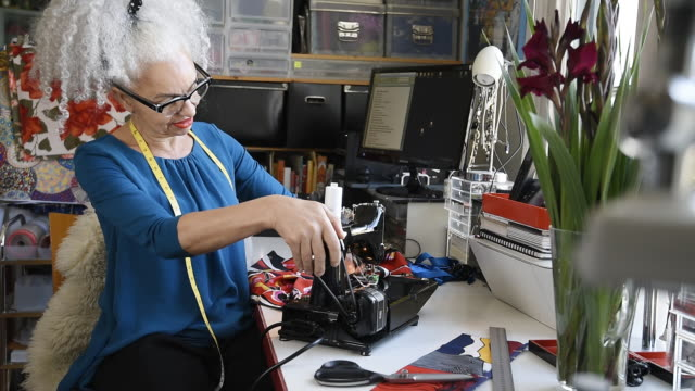 stockvideo's en b-roll-footage met senior designer using sewing machine and looking to camera - haar naar achteren