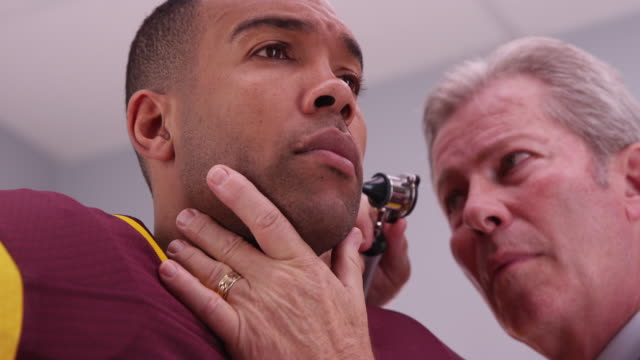 Senior doctor checking sports athlete's ear with an otoscope