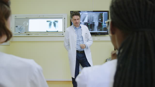 senior doctor giving presentation to team - medical record stock videos & royalty-free footage
