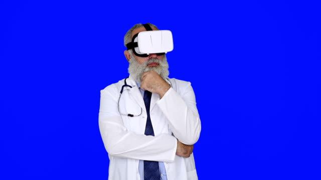 Leitender Arzt mit virtual-Reality-Brille auf einen blauen BackgroundSenior Arzt mit virtual-Reality-Brille auf blauem Hintergrund