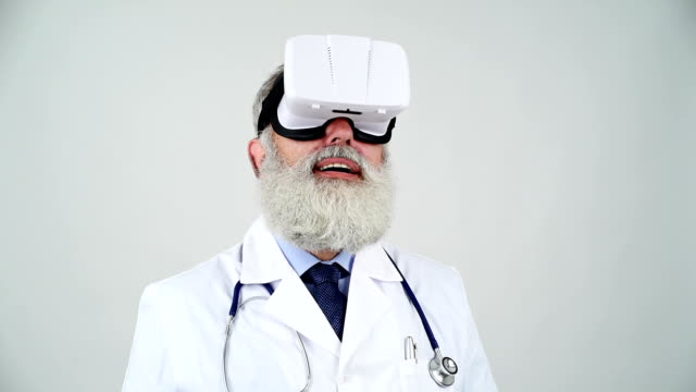 senior doctor looking at using virtual reality glasses on a gray background - shirt and tie stock videos & royalty-free footage