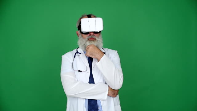 senior doctor looking at using virtual reality glasses  on a green background - shirt and tie stock videos & royalty-free footage