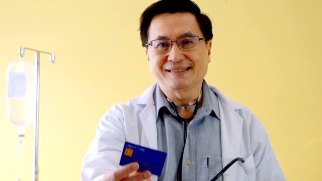 ledande läkare visar ett kreditkort - kort bildbanksvideor och videomaterial från bakom kulisserna