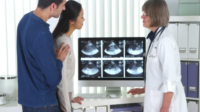 senior doctor talks to interracial couple about pregnancy scans - gynecological examination stock videos and b-roll footage