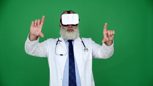 senior doctor using virtual reality glasses  on a green background - shirt and tie stock videos & royalty-free footage
