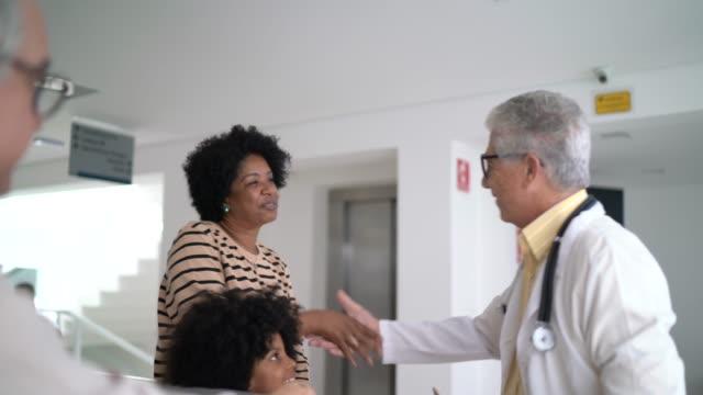 vídeos de stock, filmes e b-roll de médico sênior recebendo / cumprimentando uma família (mãe e filha) no hospital - respect