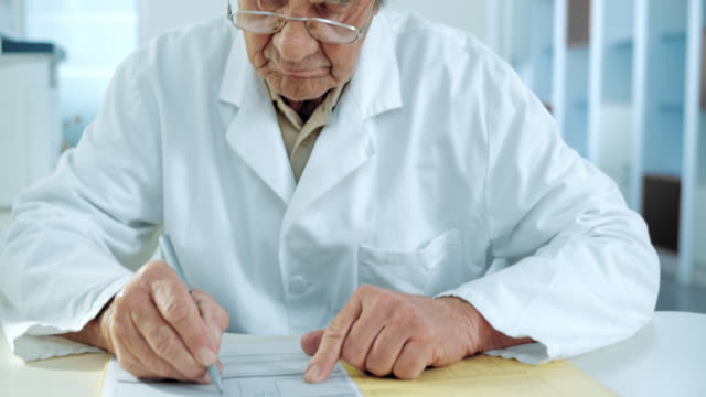 Senior doctor writing down the diagnose