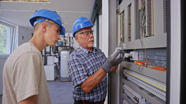 senior elektriker lära en lärling hur man ansluter kablarna i fördelnings panelen - undervisa bildbanksvideor och videomaterial från bakom kulisserna