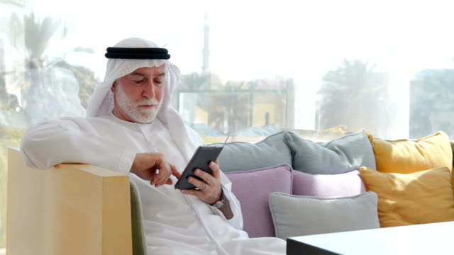 Senior Emirati man using a smartphone