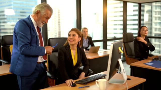 vídeos de stock, filmes e b-roll de empregado sênior que discute com a mulher de negócio no local de trabalho - teaching