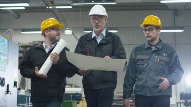Senior engineer and two workers are walking with papers through the factory space.