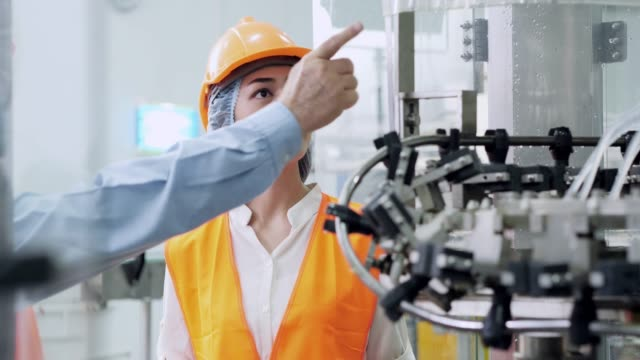 senior engineer and young woman watches as apprentices types information into computerized  and the machine starts. - pensionati lavoratori video stock e b–roll