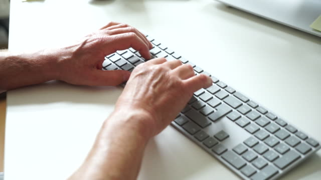 Senior entrepreneur working in his office, typing on computer keyboard