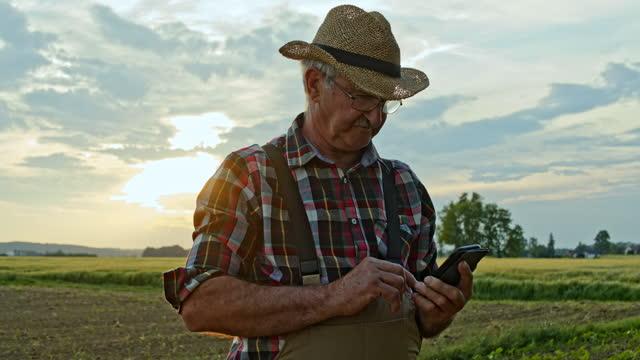 vídeos de stock e filmes b-roll de slo mo senior farmer using his smartphone while working on the field - cena não urbana