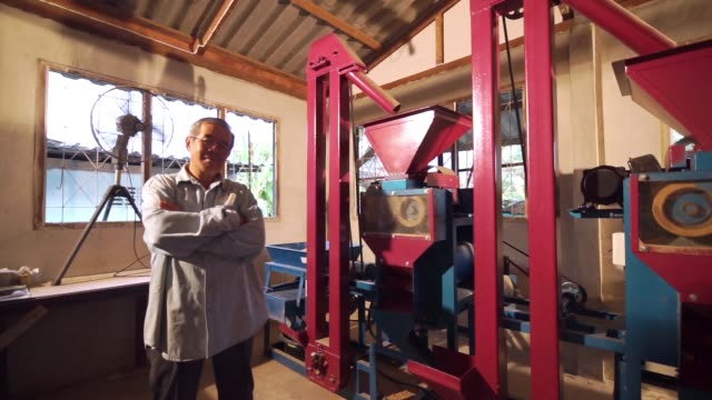 senior farmer with arms crossed standing beside a rice milling machine in the household. - rice cereal plant stock videos & royalty-free footage