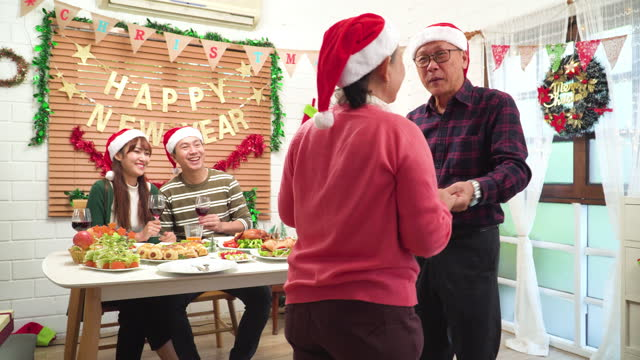 senior father dance with senior mother together while mid son, wife looking senior couple with happiness moment, southeast asian family around a lovely dinnertable for christmas to the celebration of december's holiday-decorated home. - 65 69 years stock videos & royalty-free footage