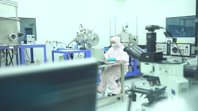 vidéos et rushes de senior femelle biologiste travaille sur son ordinateur et le microscope. - chemistry