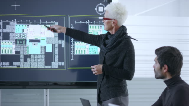 senior female caucasian architect presenting plans for the project using a large screen in the meeting room - architetto video stock e b–roll