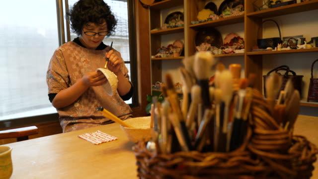 Senior female craftsmen making the traditional lacquerware