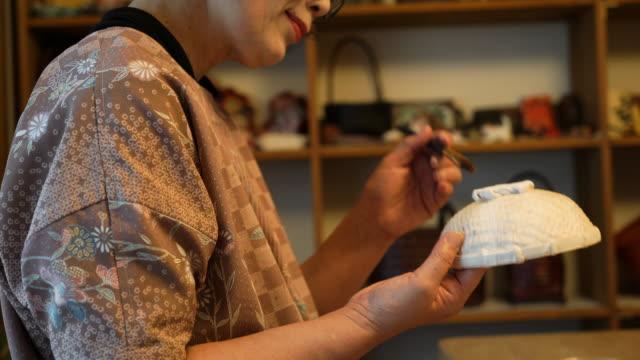 vidéos et rushes de artisans féminins seniors fabriquant la laque traditionnelle - artisanat