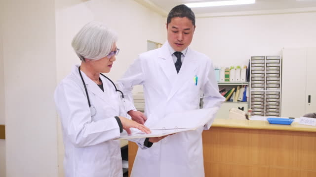 senior kvinnlig läkare och manlig kollega i tokyo hospital - sjuksköterskereception bildbanksvideor och videomaterial från bakom kulisserna