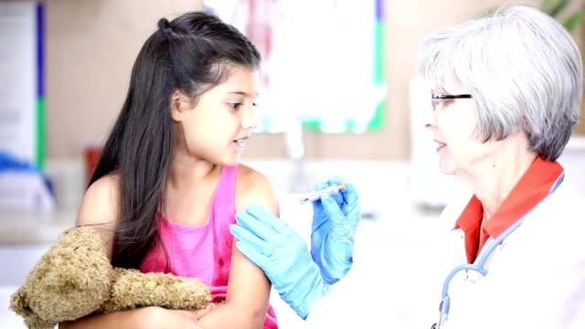 senior kvinnliga läkare, latinsk härkomst kvinnliga patienter i barnläkares office. - injicera bildbanksvideor och videomaterial från bakom kulisserna