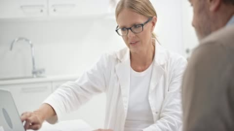 senior female doctor pointing out the values on the computer to her male patient sitting in her office - medical clinic stock videos & royalty-free footage