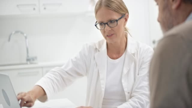 Senior female doctor pointing out the values on the computer to her male patient sitting in her office