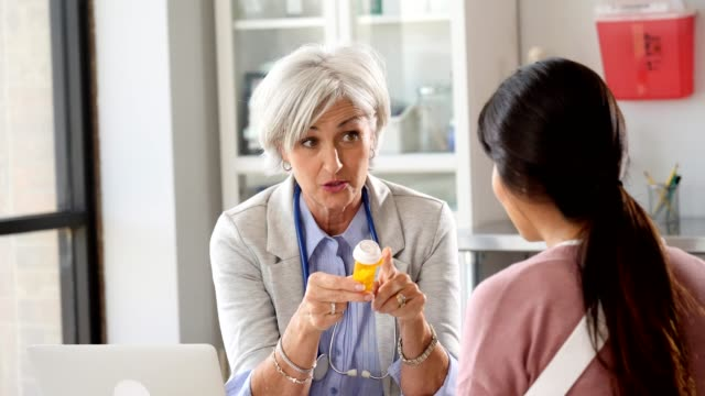 Senior female doctor prescribes pain medication with patient with arm injury