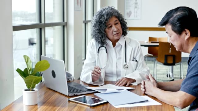 senior female doctor reviews test results with senior male patient - worried stock videos & royalty-free footage