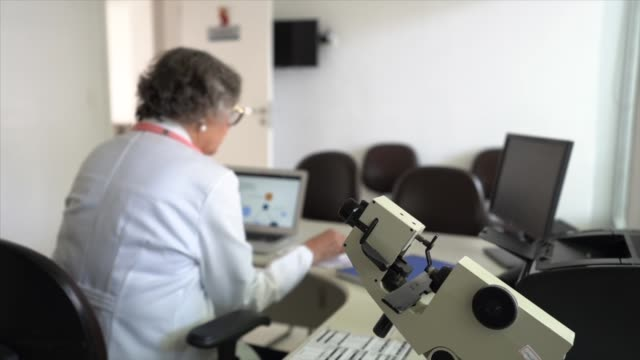 senior female doctor using laptop at doctor's office - optical equipment stock videos & royalty-free footage
