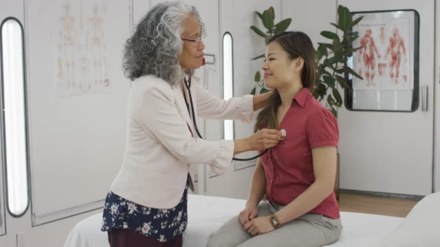 senior female doctor using stethoscope - pacific islander doctor stock videos & royalty-free footage