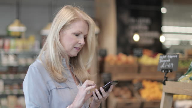 Senior female doing weekly grocery shop using smartphone