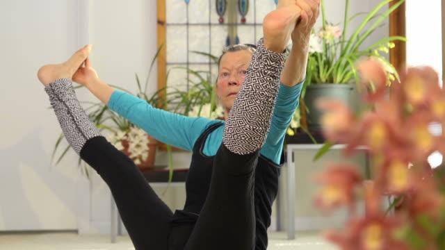 senior female doing yoga - stretching stock videos & royalty-free footage