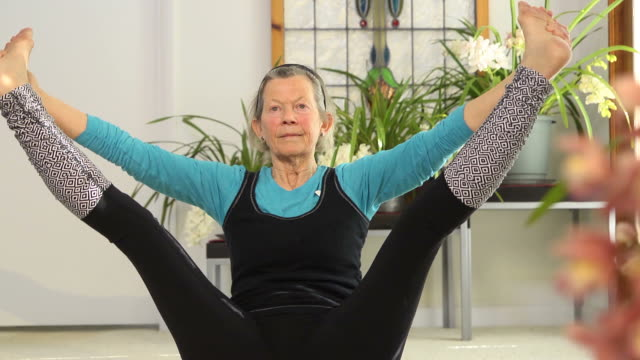 stockvideo's en b-roll-footage met senior female doing yoga - benen gespreid